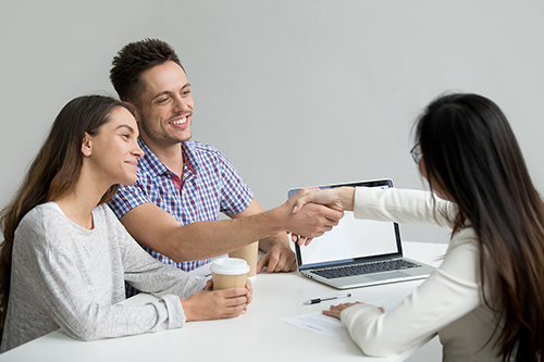 Happy millennial couple smiling, greeting advisor or consultant making good first impression. Husband handshaking real estate agent after successful contract signing, closing deal, making agreement